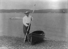 Theodore Roosevelt standing with a canoe and holding an oar on September 11, 1905.