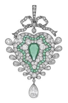 AN ANTIQUE EMERALD AND DIAMOND PENDANT/BROOCH. The heart shaped pendant featuring a central pear cut emerald weighing 1.06cts, within a surround of mixed cut diamonds and emeralds, suspending a pear cut diamond weighing 0.90cts, to a bow and ribbon surmount and detachable bar brooch fitting, in 18ct gold and platinum.