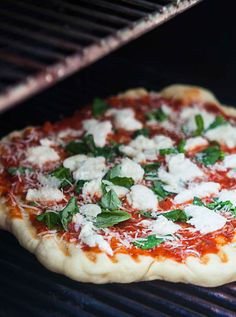 Grilling pizza is the easiest way to make pizza, and you get that great grilled flavor too. NO, the dough does not fall through the grates! See the step-by-step instructions on SimplyRecipes.com #Pizza