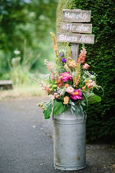 beautiful milk churn flower arrangements for the church with cute Happily Ever After Starts Here signage | onefabday.com
