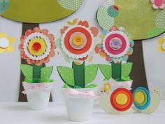 Enfeite para ser colocado na mesa do bolo ou outro lugar que preferir.  O vaso é de plástico na cor branca, a flor é feita de papel scrapbook, a grama é papel de seda rococó.  Quantidade mínima para a compra é de 10 unidades.