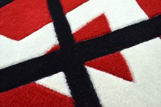 A fully Bespoke rug hand tufted with pure wool in white, black and red. It has a pile depth of 12-14mm. Created using the customers own design. [close up]