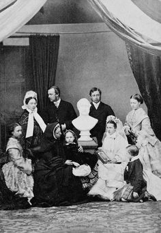 Group photograph of Queen Victoria (1819-1901) with Albert Edward, Prince of Wales (1841-1910), later King Edward VII; Princess Alexandra, Princess of Wales (1843-1925), later Queen Alexandra; Prince Louis of Hesse (1837-1892); Princess Alice (1843-1878); Princess Helena (1846-1923); Princess Louise (1848-1939); Princess Beatrice (1857-1944); and Prince Leopold (1853-1884). The family group are surrounding a bust of Prince Albert.