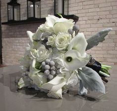 Grey and White bridal bouquet designed by Eastern Floral for a winter wedding at The Goei Center.  Flowers include White Hydrangea, white roses, white mini calla lilies, grey Brunia, and grey Dusty miller.