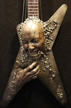Face and hand emerging from guitar by Paul Booth