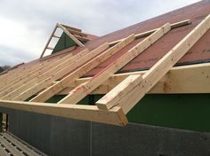 """If a house is framed without any roof overhangs, it's easier to seal the seam between the wall sheathing and the roof sheathing. This approach creates an exterior air barrier that is nearly airtight. Once the sheathing seams have been sealed, an """"applied eave"""" is framed with 2x4s to create the necessary overhang. On this roof, the gaps between the 2x4s will be filled with 3 1/2-inch-thick rigid foam insulation. The same insulation will cover the entire roof deck."""