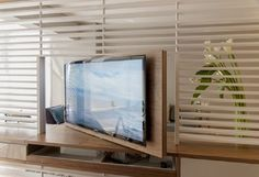 TV swivels within a partition to service two separated interior spaces