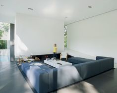 Govaert and Vanhoutte Architects Bruges, Belgium The concrete chimney wall of the living area is suspended over the hearth. A ramp on the northeast side of the house leads up to the second-level bedrooms for the son and daughter.