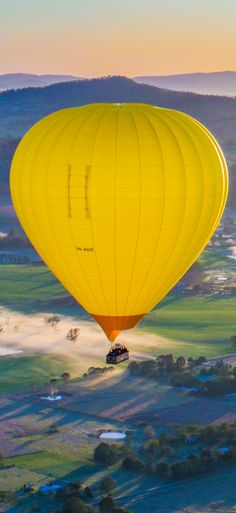 Backlighting highlights the gorgeous yellow envelope of our hot air balloon as it flies over Gold Coast countryside with stunning views of the ranges. www.hotair.com.au/goldcoast