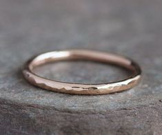 This listing is for ONE band only. This simple yet elegant band is great for everyday wear. Great to pair it with my other rings or stack a couple for a more dramatic statement. Dont let the delicate look fool you as this is a very sturdy, pretty ring. It will become one of your go to pieces in your jewelry wardrobe. This ring is hand forged in solid 14k rose gold. It is about 1.8mm wide and 1.5mm thick. It is over 60% more gold than a ring that is 1mm x 1mm. The ring is textured and highly…