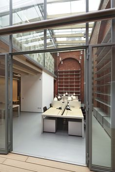 In the full-height nave are two 'Sushi Workstation' desk systems, drenched in light, which serves to emphasise the clear colour of wood. Fully equipped with ducts and partition walls, they are completed with a 'Bureau' chest of drawers and 'Plate' chairs.