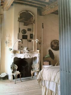 Rustic: old beams,  chalky gray floor, creamy aged plaster walls, casual bedding... added to  Refined: elegant fireplace, crystal sconces, tall trumeau. From the book Living in Provence by Barbara and Rene Stoeltie via Velvet & Linen blog.