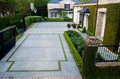 Private drive built with gray cement and framed with red brick. Grass framed. Boxwood hedges frame an english rose garden to the right and fig ivy cover the house wall.