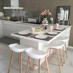 Kök med betongvägg och plexiglas bakom diskho och spis.
