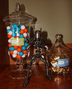 Robot Power Station / Power Supplies (orange, blue and white gumballs) and Batteries (mini Hershey bars in gold and silver wrappers) guarded by a mini robot. - Robot Birthday Party