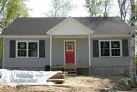 Light blue house, black shutters, red door.