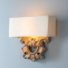 Classical Carved Sconce With a sophisticated approach to classic French design, this wall sconce blends refinement with a casual feel. Its clean, architecturally influenced design combines timeless carvings in a rich Patina Oak finish with a crisp beige fabric shade.