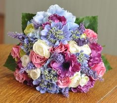 This is a beautiful bouquet made of silk raspberry roses, blue hydrangeas with touches of purple lavender, scabiosa and lavender throughout.