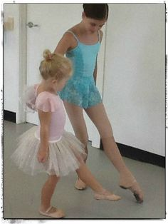 an older dancer teaching a younger dancer to point her foot