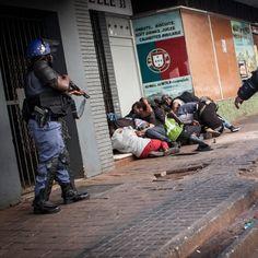 Un gruppo di manifestanti si mette al riparo dalle violenze scoppiate durante le proteste nel quartiere di Braamfontein, a Johannesburg. Gli studenti sudafricani protestano da settimane contro l'aumento delle tasse universitarie