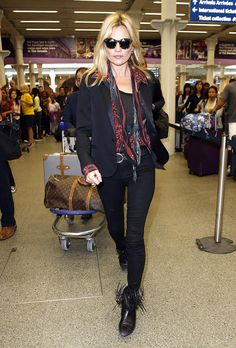 Kate Moss in all black, fringe booties, and a scarf.