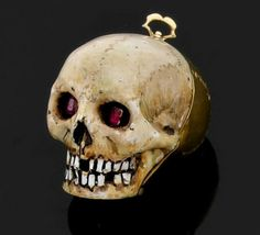 17th century memento mori skull medallion, France - Just over an inch tall with an enamel face, ruby eyes, and a yellow gold skull, it hinges open to eight interior compartments