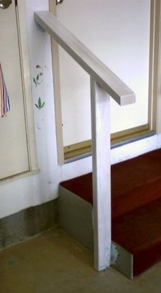 The garage steps leading into the house need a small handrail. Build out of sanded redwood, this rail is simple and functional. The vertical post is firmly mounted with concrete screws into both the step and the floor and is secured with galvanized brackets.No screws are exposed on the top rail.The finished rail is primed …