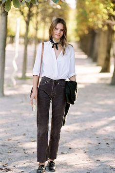Model Tilda Lindstam looks too cute with a neck scarf, white button-down shirt and corduroy pants.