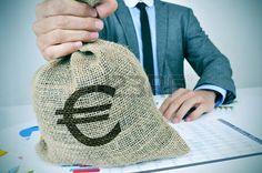 Un hombre caucásico joven tiene una bolsa de arpillera de dinero con el signo euro en la mano.