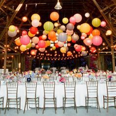 Lanterns in different colors and sizes glitter over flowers. #weddingdecor