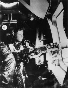 A waist gunner of VB-103 Squadron, US Navy in position inside a B-24 Liberato
