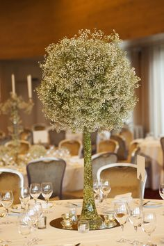 Tall clear vases filled with delicate baby's breath with a large ball shaped arrangement of baby's breath
