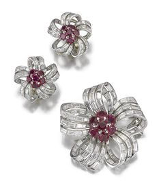 RUBY AND DIAMOND DEMI-PARURE, 1950S.  Comprising: a brooch set with circular-cut rubies to the centre and baguette diamond open work petals, one diamond deficient, together with a pair of ear clips en suite.