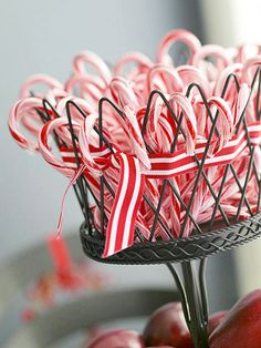 Simple Stripes        Stuff iconic candy canes into a decorative bowl or flowerpot, and add red-and-white stripe ribbon for a coordinating touch.
