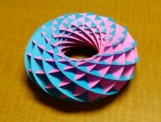 I made another thing! This is a torus, made from 24 crescent-shaped pieces of paper with slots cut into them so they interlock with each other. I followed these instructions on cutoutfoldup.com. Th…
