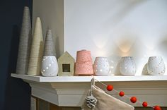 simple and beautiful mantle. love those wrapped trees, touch of red and the candlelight.