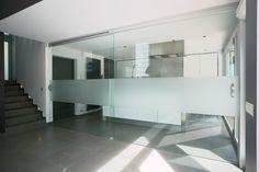 Grote glazen schuifdeuren met gezandstraald glas en een aluminium rail en grepen. Op maat gemaakt door Anyway Doors.