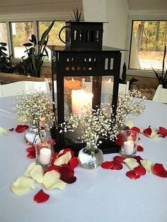 A tablescape with a black lantern holding a pillar candles surrounded by small vases of baby's breath and scattered white and red rose petals.