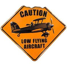 Careful overhead, we're flying low! Featuring embossed black letters, a black background, and the image of a single propeller plane, Low Flying Aircraft Metal Sign is perfect for a multitude of people. Hang this clever sign in your office, man cave, den, living room, hallway, and more!