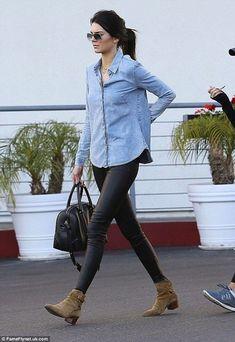 Kendall Jenner wearing Light Blue Denim Shirt, Black Leather Leggings, Olive Suede Ankle Boots, Black Leather Duffle Bag