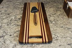 THIS ONE OF A KIND BOARD IS MADE OF BRAZILIAN WALNUT, MAPLE , AND PADUAK WITH 4 SOFT ANTI SLIP RUBBER FEET. FINISH IS MINERIAL OIL AND BEESWAX MEASURES 15 1/2 X 11 1/2 X 3/4 THICK, THE HANDLE IS 9 TO BOOTTOM OF TAPER BIG ENOUGH AS A FULL SIZE CUTTING BOARD LIGHT ENOUGH TO BE USE AS A