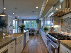 Family and friends are sure to gather and make memories in this dream kitchen. Details, from the high-end gas range to the wire-brushed flooring, set this cooking space apart.