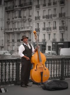 Black and White photo of a Jazz Bassist playing on the street in Paris by Notre Dame. Description from martinsoler.com. I searched for this on bing.com/images