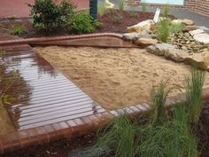 Sandpit at a kindergarten - i like the natural aspects, stage and sand area - just need to add a storage box and cover.