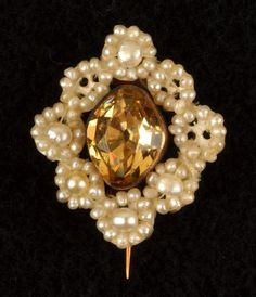 Oval faceted yellow topaz pin in metal setting with hinged pin and hook on reverse, surrounded by seed pearls beaded to perforated mother of pearl frame, arranged in a diamond shape. New-York Historical Society, Z.2262.