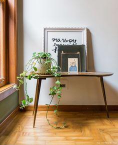 Hall que leva aos quartos tem mesinha de madeira, vaso com plantas e quadros.