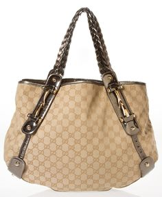 """Gucci Canvas Monogram Shoulder Bag  Classic Gucci monogram canvas is trimmed with a gunmetal bronze leather and goldtone hardware.  Braided shoulder straps and leather trim.  The leather is cracking a bit as I must have kept it stored in poor condition, but the bag is in overall great condition with much use left in it! The interior has a small stain, which does not affect the use of the bag.  Flat zip interior pouch  16"""" x 12"""" x 4.5"""" with a strap drop of 8"""" MATERIAL:Canvas, Leather"""