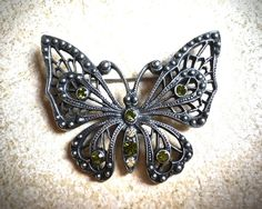 Green rhinestone butterfly #vintage brooch   This larger vintage butterfly brooch measures 2 1/4 wide x 2 inches long. Its gunmetal gray and has 6 emerald green rhinestones ... #etsy #jewelry #necklaces #valentines