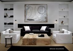 stylish contemporary white living room with slip covered sofas, rustic wood block coffee table and gorgeous artwork