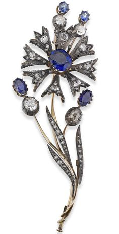 An early 20th century sapphire and diamond 'en tremblant' brooch  The brooch modelled as a spray of cornflowers, the central oval-cut sapphire with diamond tipped stamen surround, old round brilliant-cut diamond petals, issuing four oval-cut sapphire and rose-cut diamond set buds, the foliage with diamond detailing, length 85mm, the sapphires estimated to weigh approximately 4.30cts in total